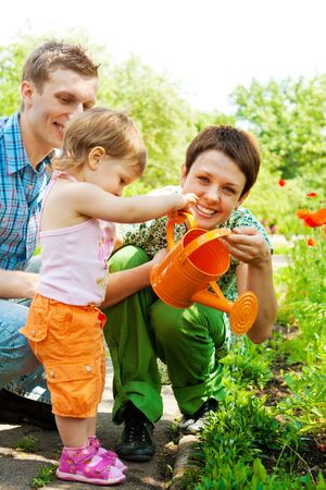 watering plants: Family watering plants in the garden