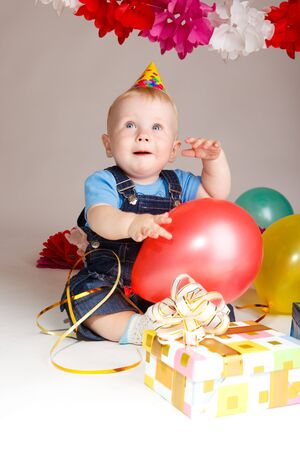 Baby boy with balls and birthday presents photo