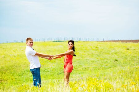 Happy couple holding hands in the field Stock Photo - 5526900