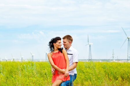 Loving couple standing in the field with wind turbines Stock Photo - 5526937