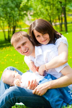 Cheerful family having fun in the summer park photo
