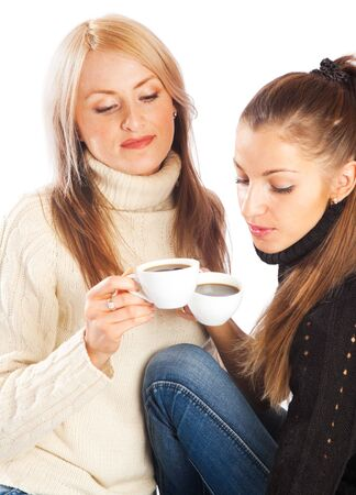 Two lovely girls in black and white sweater having coffee photo