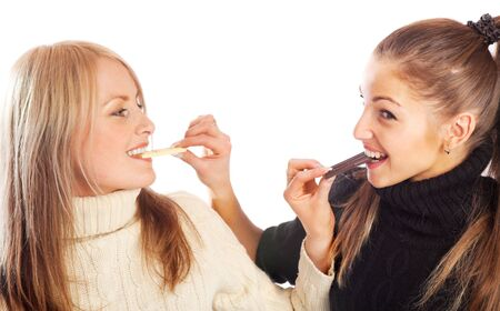 Two girls eating black and white chocolate photo