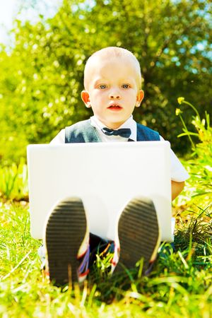 Toddler with laptop, sitting in the park photo