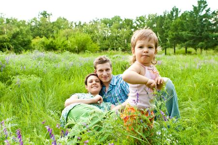 Young family in green grass photo