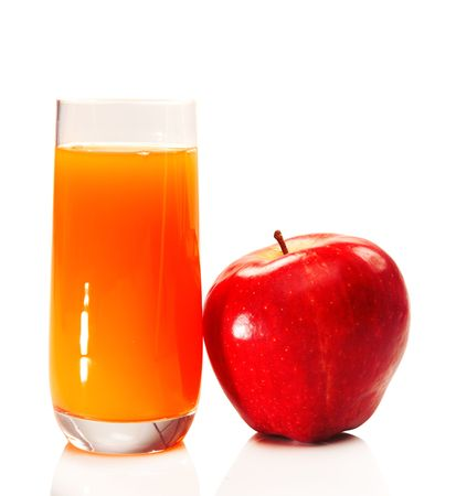 Red apple beside a juice glass, isolated photo