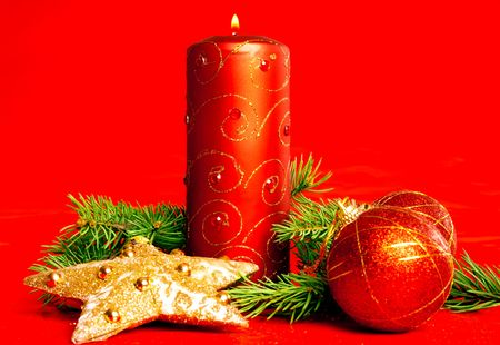 Christmas candle and decoration over red photo