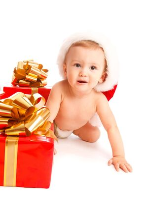 Baby in santa hat crawling near Christmas presents photo