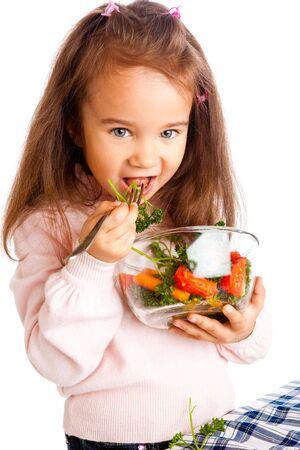 Preschool girl eating vegetable salad photo