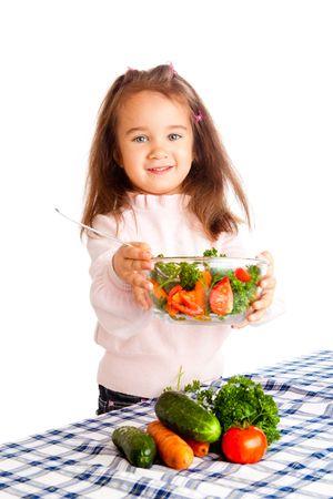 Preschool girl giving vegetable salad photo