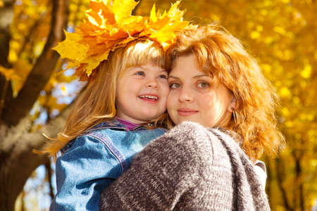 Portrait of mother and daughter in the autumn park photo
