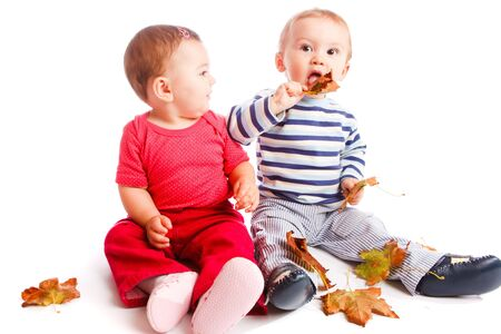 babies playing: Babies playing with autumn leaves Stock Photo