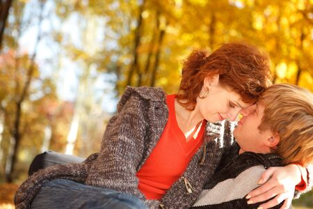 Young couple sitting on yellow leaves in park Stock Photo - 5670806