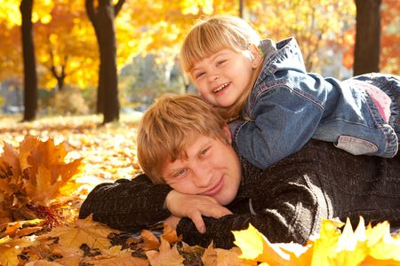 Daddy and doughter in autumn park lying on yellow leaves photo