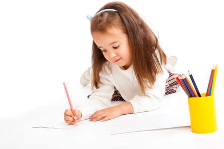 Preschool girl drawing an image with a pencil photo