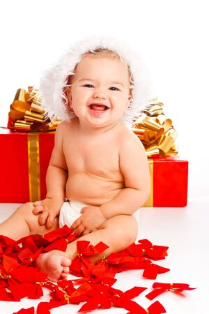 Lovely baby girl in santa hat sitting near xmas presents photo