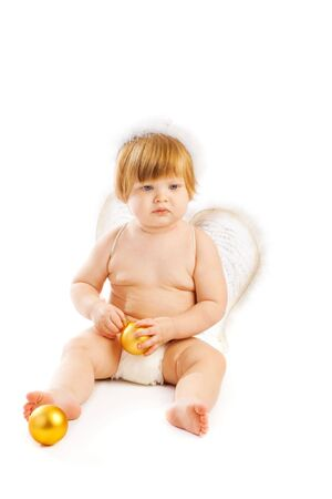 A cute baby angel holding golden Christmas decoration photo