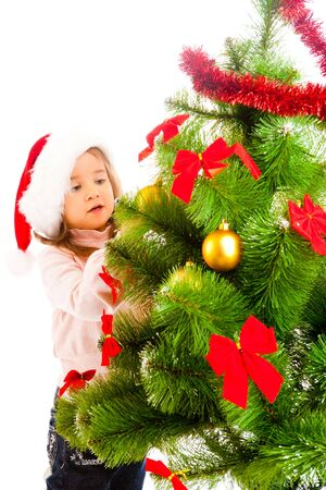Cute girl helping to decorate Christmas tree photo