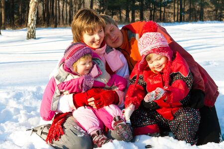 Lovely cheerful family having fun in the winter park photo