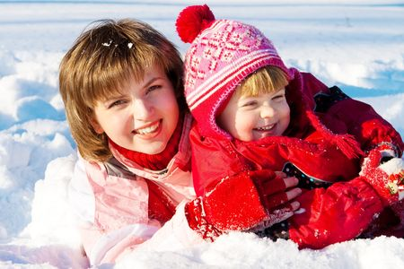 Happy mother and her preschool daughter playing in snow photo