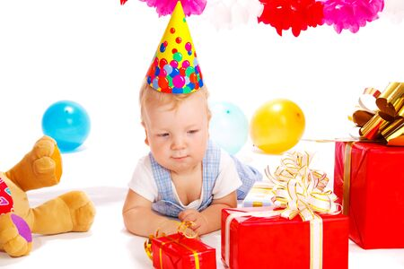 Baby in a party hat unpacking presents photo