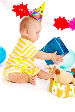 Baby in a party hat holding his birthday present photo