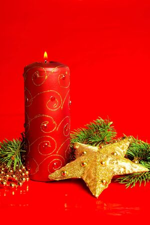 A candle and Christmas decoration on red background photo
