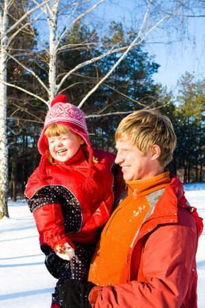 Happy father holding his daughter in a snowy park photo