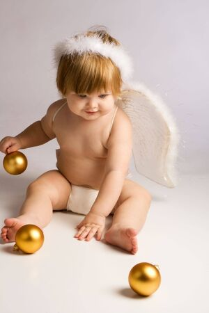 Baby angel playing with golden Christmas decoration photo