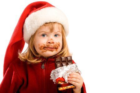 Portrait of a preschool girl in santa hat eating chocolate photo