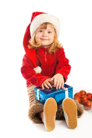 Cute preschool girl in santa hat holding  Christmas gift photo