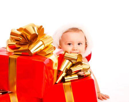 Baby boy hiding behind a heap of Christmas presents photo