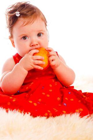 Cute baby girl eating a ripe peach photo