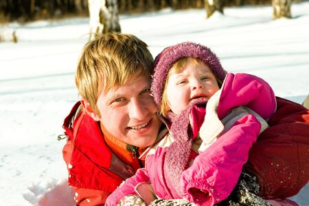 Happy father and daughter playing in snow photo