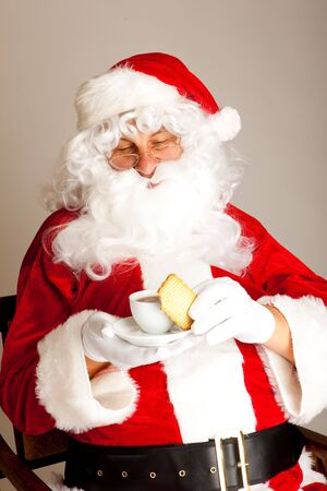 Santa Claus sits in chair and enjoying coffee time photo