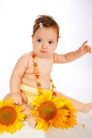 Beautiful baby girl in a yellow dress with sunflowers photo