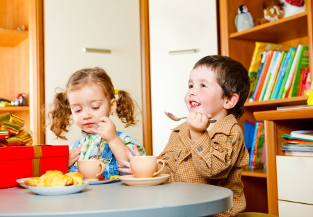 kid eat: Boy and girl sitting at the table and having tea with cookies