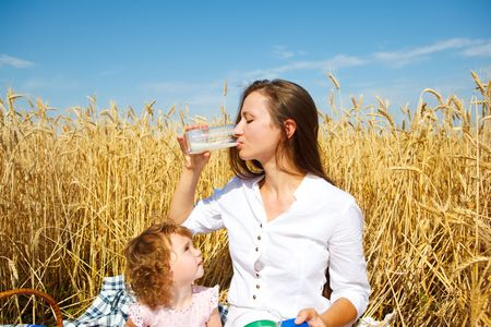 Mother and daughter in a wheat field. Mother drinking milk. photo