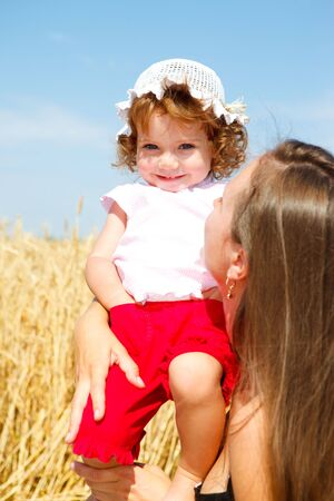 Lovely smiling girl in mothers hands photo
