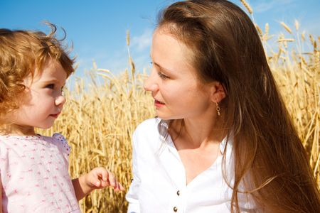 Cute curly girl and her mother talking in the wheat field photo