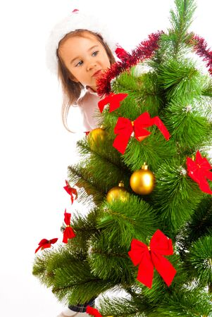 Lovely preschool girl hiding behind Christmas tree photo