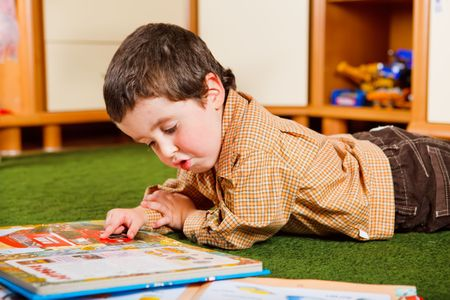 kids reading book: Smart preschool boy reading a large book Stock Photo