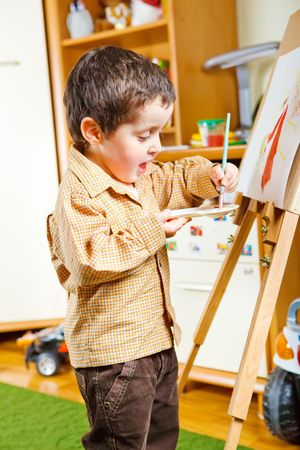 Cute preschool boy painting photo
