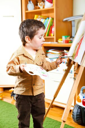 kids painting: Smart preschool boy painting in his room