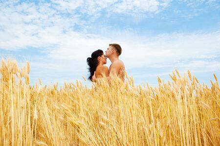 Romantic couple standing in a wheat field photo