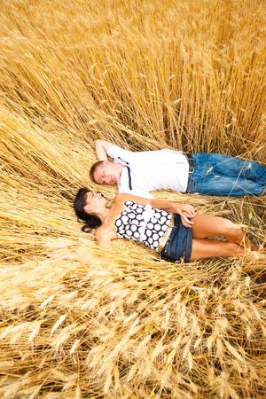 Adorable couple lying in wheat photo