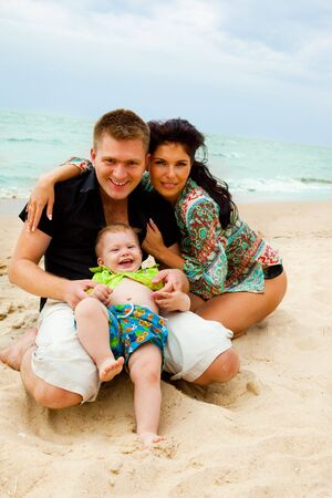 Happy kid and his parents at the coastline photo
