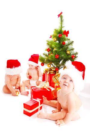 Santa babies beside Christmas tree photo