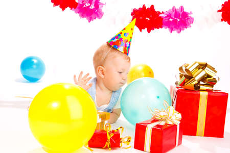 Baby in a party hat looking at presents photo