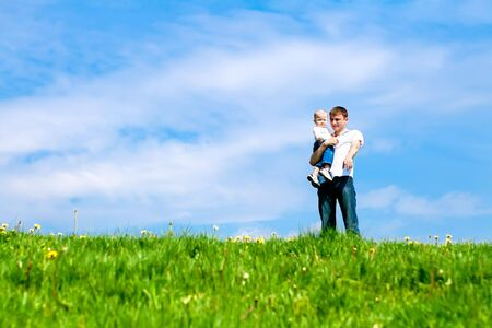Father and son standing on the spring meadow Stock Photo